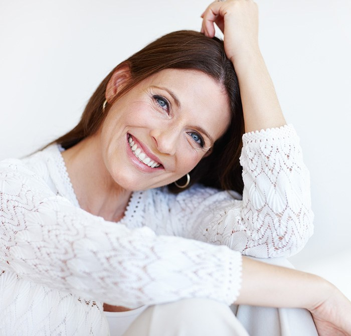 Happy mature woman spending time at home, smiling softly and relaxed