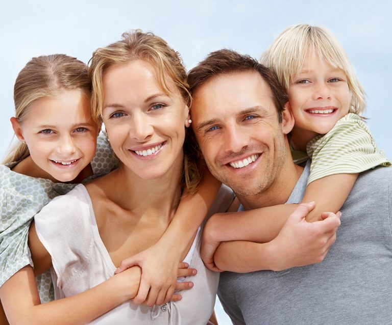 Family of father, mother, and two children close together and bonding outside