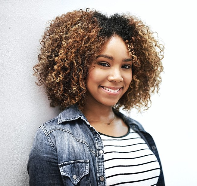 Closeup shot of a young woman smiling, posing against a white background